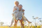 Senior Mann trägt seine Frau auf dem Rücken, er hat eine gesunde Wirbelsäule - 175855231