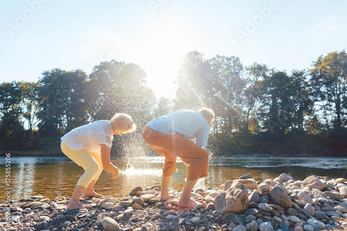 Two senior people enjoying retirement and simplicity while throwing stones into the river