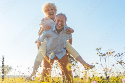 Leinwandbild Motiv Senior Mann trägt seine Frau auf dem Rücken, er hat eine gesunde Wirbelsäule