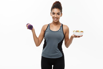 Healthy and Fitness concept - Beautiful sporty African American on diet holding dumbbell and fresh salad on hands. Isolated on white studio background. © Benzoix