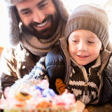 Dad and son taking sweets on traditional Christmas market - 175863212