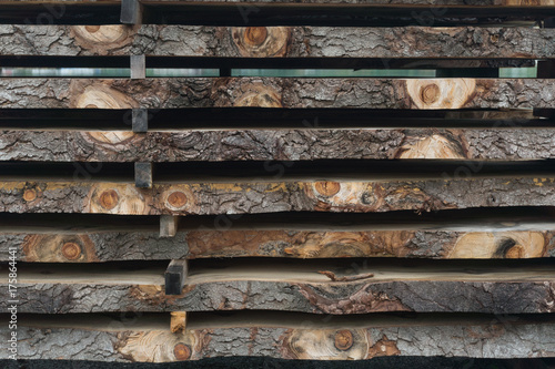 Sawn logs stacked in a pile at the sawmill Poster