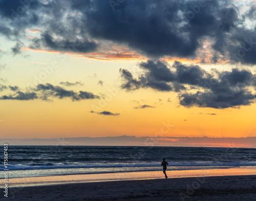 Fotobehang Strand Jogger am Strand bei Sonnenuntergang bei Cadiz