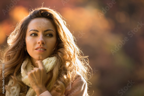 Close up portrait of cute woman in autumn day at park look at side, blurred background