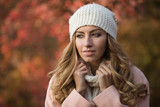 Pretty woman portrait in white hat at the autumn day, she standing in park, colorful foliage around