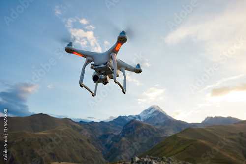 drone copter flying with digital camera in mountains