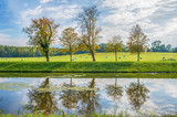 Riverside. Early autumn landscape with small river and blue sky. Man's island,Chiemsee,Bavaria,Germany - 175874676
