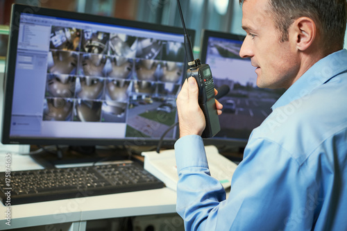 Security worker with radios. Video surveillance system. - 175874635