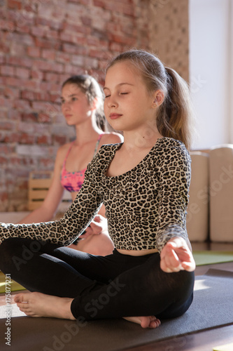 Staande foto Zen Zen life for child. Self-improvement. Young meditating girl in yoga studio, teenage sport in focus on foreground. Gym background, healthy lifestyle, thoughts concentration