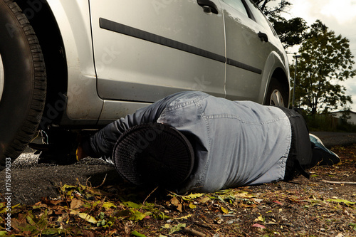 Criminal installing plastic explosive under car outdoor on parking place Poster
