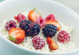 Organic cottage cheese with blackberry, strawberry and raspberry in a white ceramic bowl on the kitchen table. Dairy products for the breakfast. Healthy food concept. - 175880034