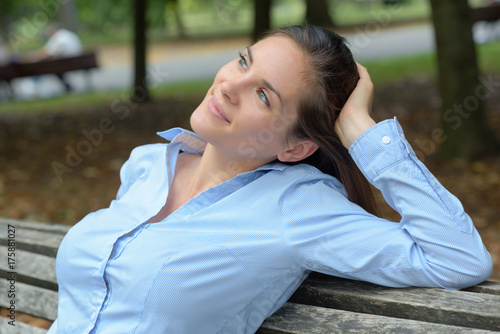 Plakát woman sat on park bench with dreamy expression