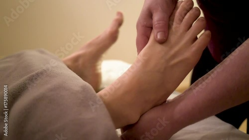 Tuinposter Gymnastiek Using a type of ointment a massage therapist works on loosening up the muscles and tendons in a mature, caucasian woman's toes and feet.