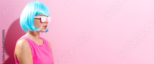 Keuken foto achterwand Kapsalon Portrait of a woman in a bright blue wig on a pink background