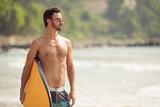Surfer man with surfboard on sea coast. - 175895092