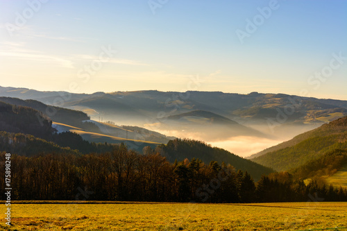 Keuken foto achterwand Ochtendgloren Scenic color image of a foggy winter morning sunrise over a rural hilly landscape with fields,forest, fog in valley, under blue sky with some clouds and a wide view towards the horizon