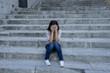 beautiful and sad Hispanic woman desperate and depressed sitting on urban city street staircase