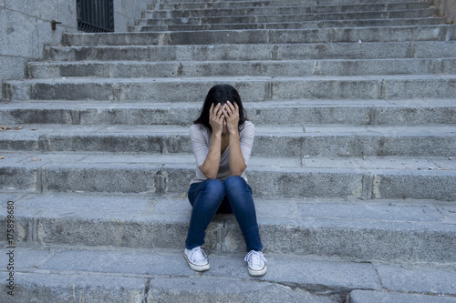 Deurstickers Wanddecoratie met eigen foto beautiful and sad Hispanic woman desperate and depressed sitting on urban city street staircase