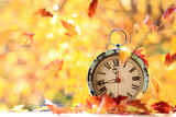 Autumn leaves blowing in the wind across an antique alarm clock