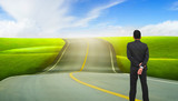 businessman standing and looking on the road. road to success concept.
