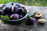 Ripe plums in plate on wooden background - 175908619