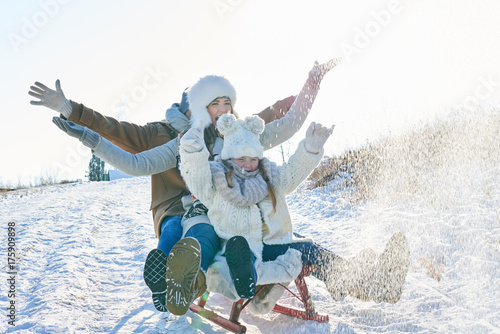 Plakat Familie beim Rodeln und Schlitten fahren im Winter