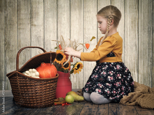 little girl goes through autumn bouquet of flowers of sunflower, ears of wheat. The basket of vegetables, the harvest from the village. The concept of gifts of autumn, vitamins from vegetables,