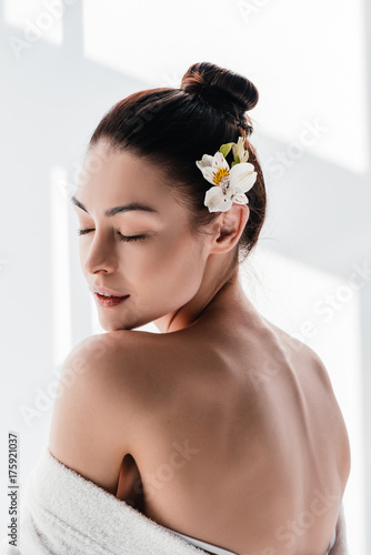 Young woman with lily in hair