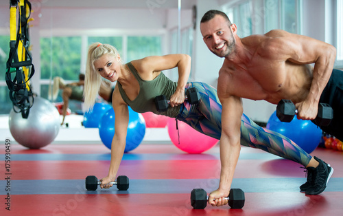 Young couple working out with dumbbells at gym