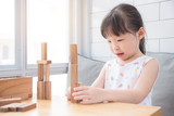 Little asian girl playing wooden blocks on table in living room - 175930877