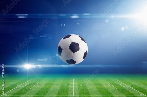 Soccer ball on soccer stadium with bright light flare in night