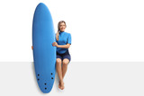 Female surfer with a surfboard sitting on a panel - 175935492