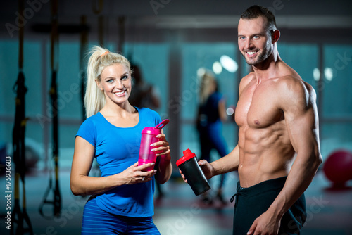 Tuinposter Gymnastiek man and woman with protein shake at gym