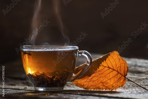 Papiers peints The Transparent cup with tea and autumn yellow dry leaf on a dark background. The smoke is curly from the cup. Autumn mood of coziness and warm atmosphere.