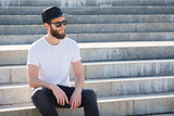 Hipster handsome male model with beard wearing white blank t-shirt with space for your logo or design in casual urban style - 175939641
