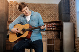 Pleasant young man playing guitar - 175940829