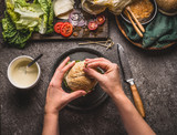 Female women hands holding homemade tasty burger  on rustic kitchen table background with ingredients, top view - 175940880