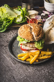 Homemade tasty burger with chicken, lettuce, mozzarella and tomatoes served with french fries potatoes on rustic kitchen table background, front view - 175941049