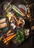Various colorful organic vegetables ingredients from local market on dark rustic kitchen table background with pot, spoon, plates, knife and ingredients for tasty vegetarian cooking, top view. - 175944628