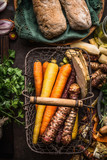 Colorful root vegetables in harvest basket on dark wooden kitchen table background, top view. Healthy and clean food and eating  concept. - 175944827