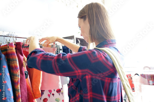 Woman in clothing store, shopping day - 175945449
