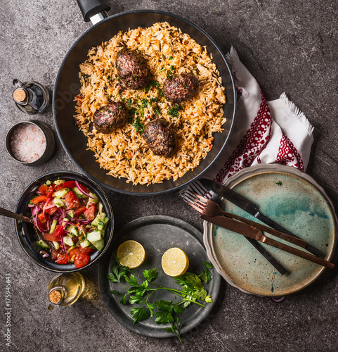 Meat balls with vegetables rice in pan and salad, served on gray stone kitchen table background with plates and cutlery, top view