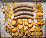 Fried sausages on baking tray with baked apples, onions and lye bun toast , top view, close up. German food - 175945807