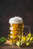 Mug of fresh beer with cap of foam and hops on dark background, front view - 175945855