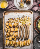 Fried sausages on baking tray with baking apples, onions and lye bun toast with mustard dip, top view. - 175947059