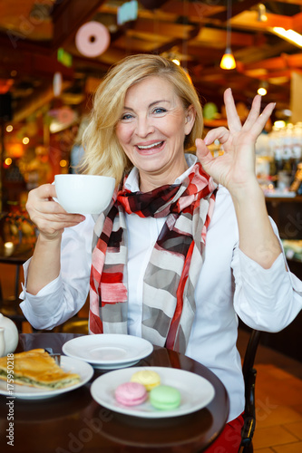 Smiling and happy old senior business woman sitting in cafe with tea cap and show gesture Ok Poster