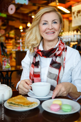 Portrait of smiling and happy old senior business woman sitting at table in cafe Poster