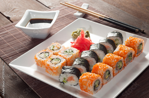 Foto op Canvas Sushi bar Sushi rolls on a black and white plate, on a wooden mat with chopsticks and soy sauce