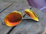 Spiegelung von Sonnenschirm und Himmel in einer goldenen Sonnenbrille - 175958263