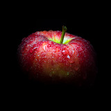 Water droplet on glossy surface of red apple on black background